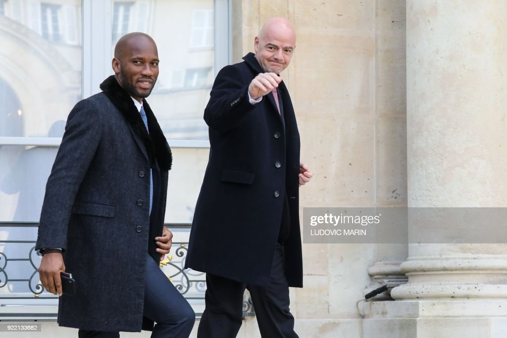 President of FIFA Gianni Infantino (R) and Ivory Coast's football player Didier Drogba arrive at the Elysee presidential palace, for a lunch with French President and Liberian President and other guests, on February 21, 2018, in Paris. /