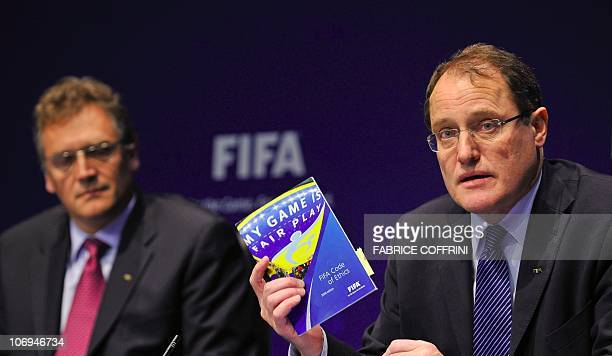 President of FIFA's ethics committee Claudio Sulser gestures with the 'FIFA's code of ethics' next to FIFA general secretary Jerome Valke during a...