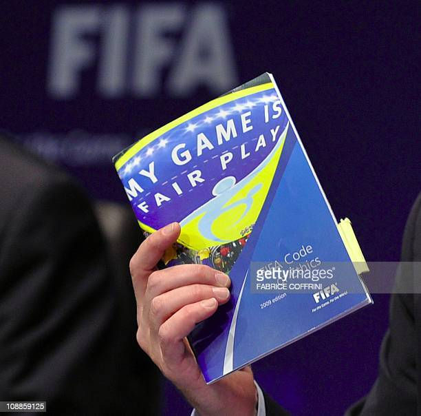 President of FIFA's ethics committee Claudio Sulser's hand holds the 'FIFA's code of ethics' during a press conference on November 18 2010 in Zurich...