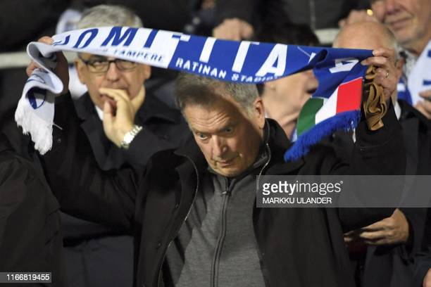 President of Finland Sauli Niinisto puts on the game scarf prior to the UEFA Euro 2020 Group J qualification football match Finland vs Italy in...