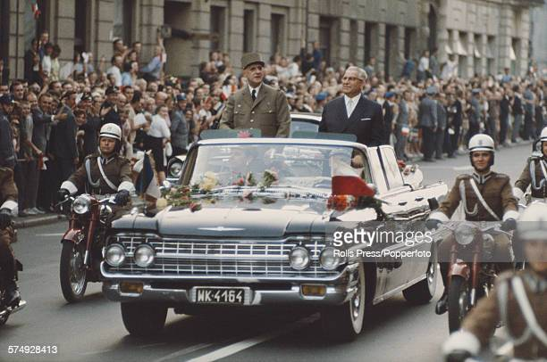 President of France Charles de Gaulle pictured standing in the rear seat platfor area of a convertible limousine with Chairman of the Polish Council...