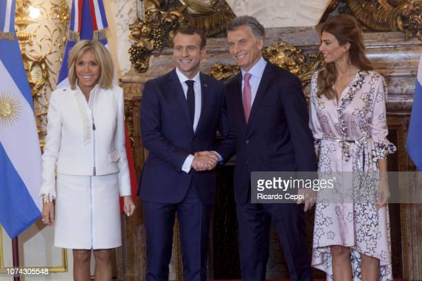 President of France Emmanuel Macron shakes hands with President of Argentina Mauricio Macri next to First Lady of France Brigitte Macron and First...