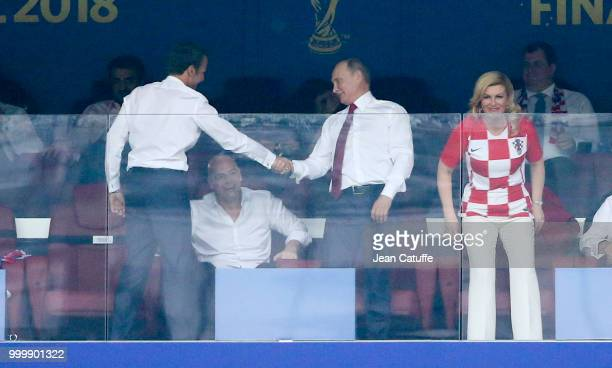 President of France Emmanuel Macron shakes hands with President of Russia Vladimir Putin while President of Croatia Kolinda GrabarKitarovic looks on...