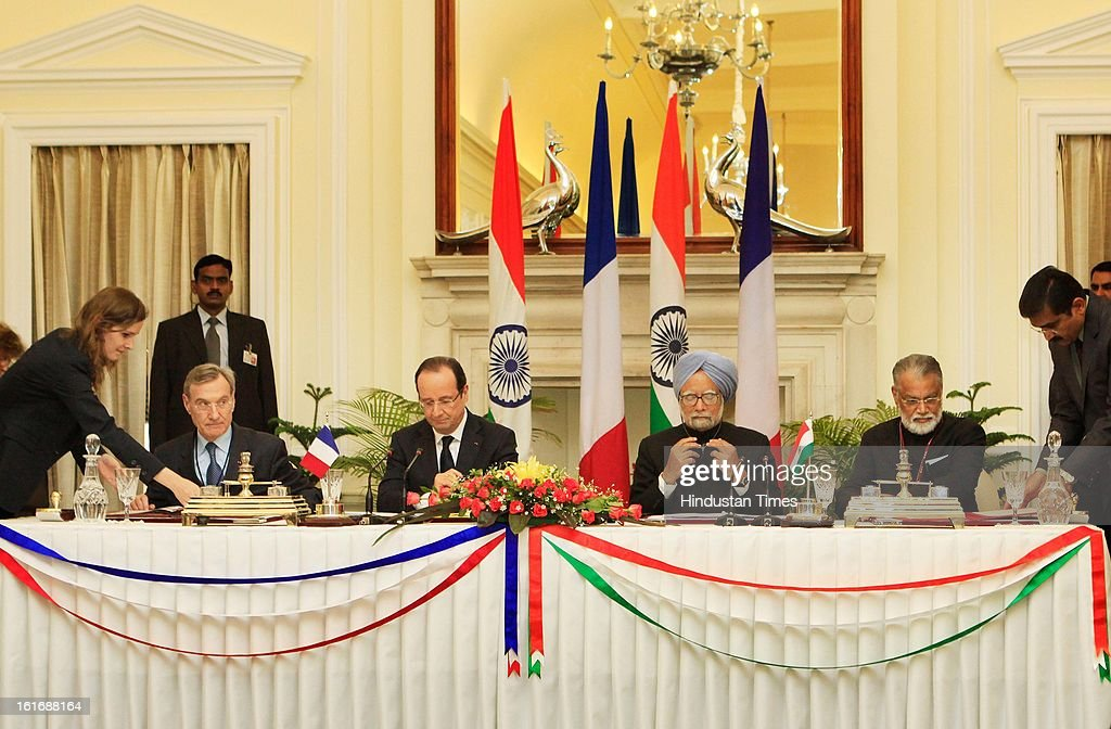 President of France's National Center for Space Research, Yannick d'escatha (L) and Chairman of Indian Space Research Organisation, Shri Radhakrishnan(R) signed an agreement in the presence of French President Francois Hollande and Prime Minister Manmohan Singh on February 14, 2013 in New Delhi, India.