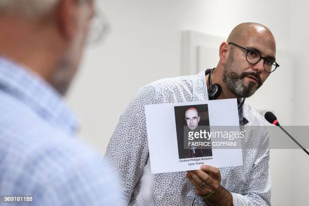 President of French association 'La parole Liberee' Francois Devaux holds a picture of French cardinal Philippe Barbarin during a press conference of...