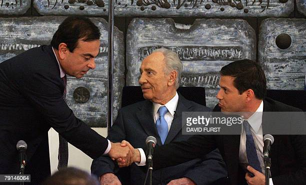 President of French automaker RenaultNissan Carlos Ghosn shakes hands with Director General of Better Project Shai Agassi as Israeli President Shimon...