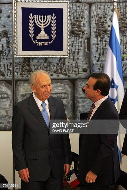 President of French automaker RenaultNissan Carlos Ghosn talks with Israeli President Shimon Peres following a joint press conference with Director...