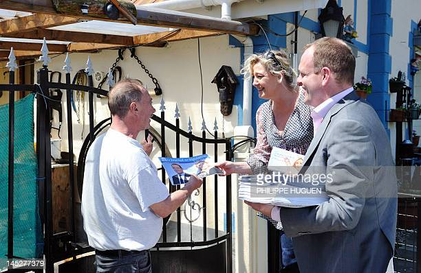 President of French farright party Front national Marine Le Pen gives an electoral flyer to a man while going door to door flanked by FN general...