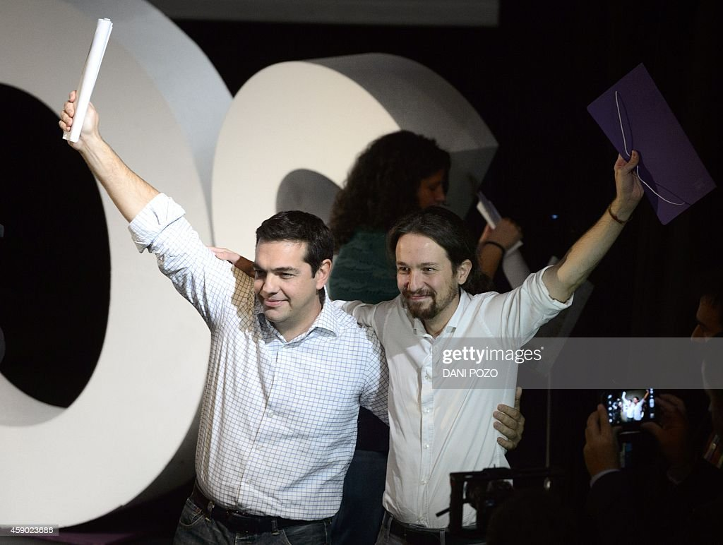 President of Greek oposition SYRIZA (Coalition of the Radical Left) Alexis Tsipras (L) and newly confirmed leader of Podemos, a left-wing party that emerged out of the 'Indignants' movement, Pablo Iglesias, wave at a party meeting in Madrid on November 15, 2014. Podemos activists confirmed Pablo Iglesias, 36 years at the head of the movement, in a vote whose results were announced today. Pablo Iglesias was elected secretary general with 88.7% of the vote (95,311 votes out of 107,488) announced the party at a ceremony attended by nearly a thousand people in a Madrid theater.