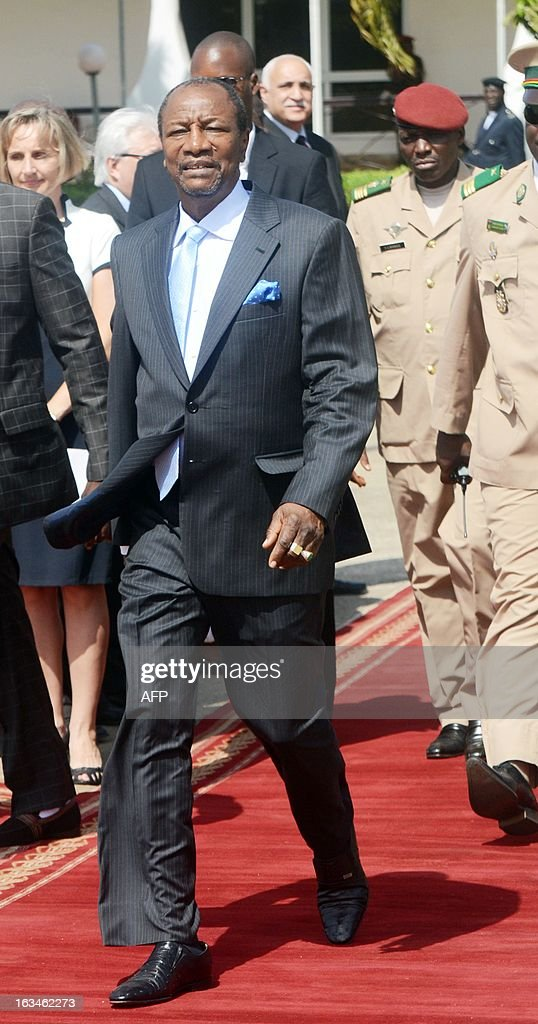 President of Guinea Alpha Conde walks on March 10,2013 at the Conakry airport, before meeting his counterparts from Ivory Coast, Liberia and Sierra Leone, as Guinea battles unrest linked to legislative elections in May.