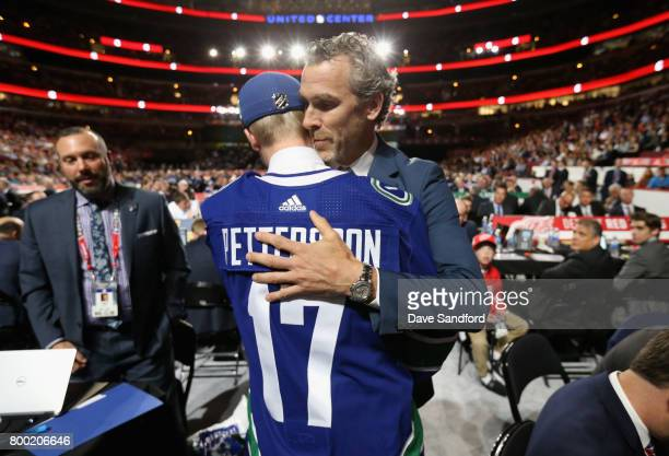 President of hockey operations of the Vancouver Canucks Trevor Linden hugs Elias Pettersson fifth overall pick of the Vancouver Canucks offstage...