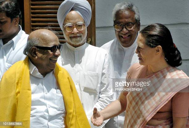 President of India's Congress Party Sonia Gandhi gestures as she speaks with Dravida Munntra Kazhagam party leader MKarunanidhi as Manmohan Singh who...