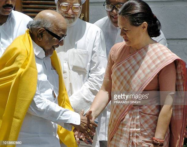 President of India's Congress Party Sonia Gandhi shakes hands with Dravida Munntra Kazhagam party leader MKarunanidhi as Manmohan Singh who looks...