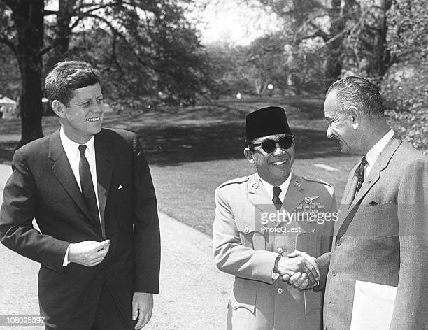 President of Indonesia Sukarno shakes hands with US Vice President Lyndon Johnson as President John F Kennedy smiles Washington DC April 25 1961