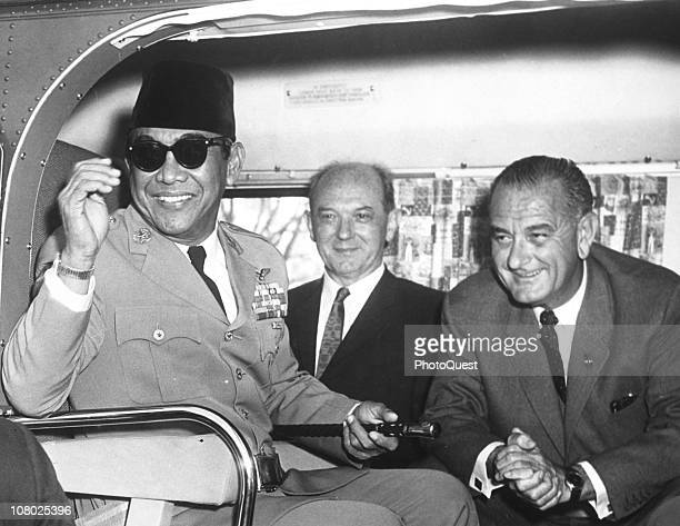 President of Indonesia Sukarno smiles as he sits in a helicopter with US Secretary of State Dean Rusk and Vice President Lyndon Johnson following...