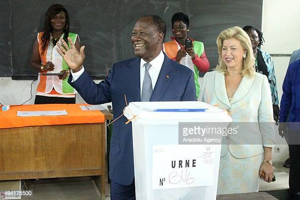 President of Ivory Coast Alassane Ouattara and his wife Dominique Folloroux-Ouattara pose after casting their votes in Saint Mary High School during...