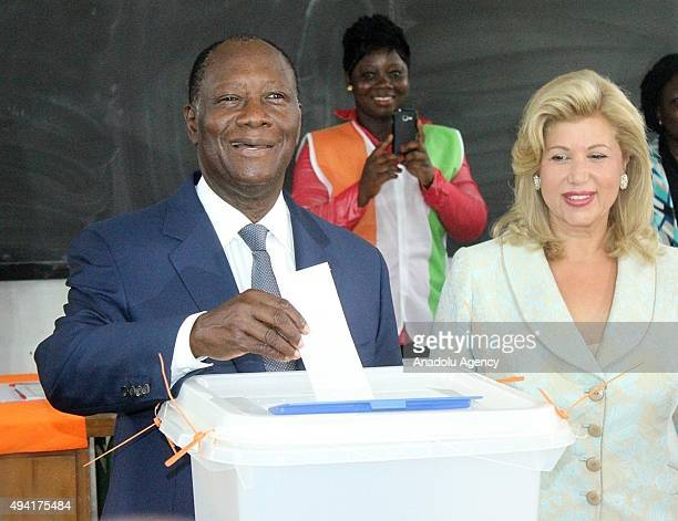 President of Ivory Coast Alassane Ouattara casts his vote while his wife Dominique Folloroux-Ouattara looks on in Saint Mary High School during the...