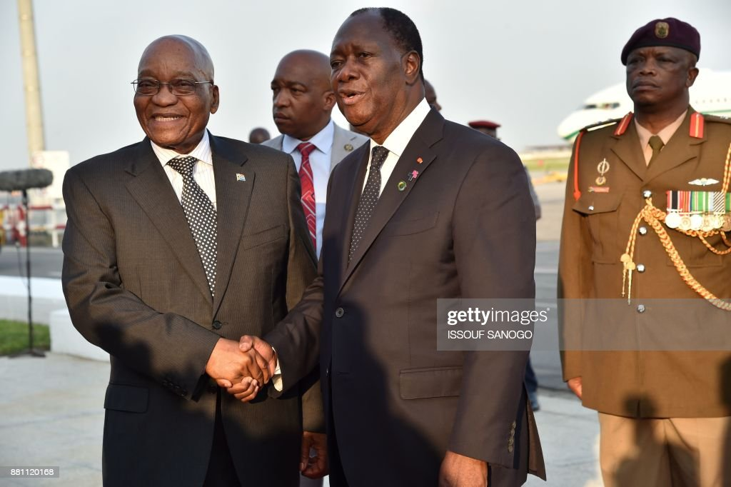 President of Ivory Coast Alassane Ouattara (C) shakes hands with president of South Africa Jacob Zuma (L) upon his arrival at the Felix Houphouet- Boigny airport in Abidjan on November 28, 2017 ahead of the Afican Union - European Union summit. /