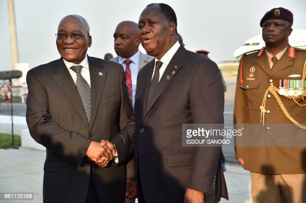President of Ivory Coast Alassane Ouattara shakes hands with president of South Africa Jacob Zuma upon his arrival at the Felix Houphouet Boigny...