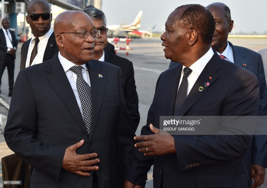 President of Ivory Coast Alassane Ouattara (C) speaks with president of South Africa Jacob Zuma upon his arrival at the Felix Houphouet- Boigny airport in Abidjan on November 28, 2017 ahead of the African Union - European Union summit. /