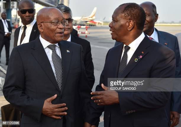 President of Ivory Coast Alassane Ouattara speaks with president of South Africa Jacob Zuma upon his arrival at the Felix Houphouet Boigny airport in...