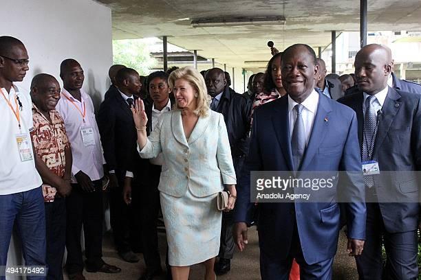 President of Ivory Coast Alassane Ouattara walks next to his wife Dominique Folloroux-Ouattara who waves to citizens before casting their votes...