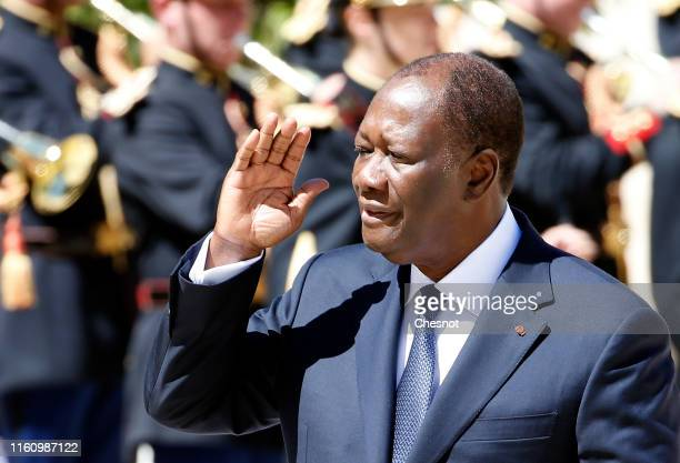 President of Ivory Coast Alassane Ouattara walks past the honor guard prior to his meeting with French President Emmanuel Macron at the Elysee...
