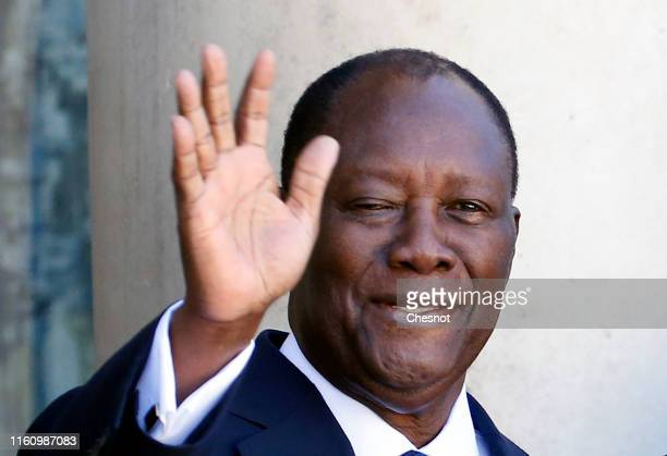 President of Ivory Coast Alassane Ouattara waves as he arrives for a meeting with French President Emmanuel Macron at the Elysee Presidential Palace...
