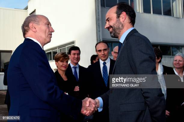 President of leading world cosmetics group L'Oreal JeanPaul Agon shakes hands with French Prime Minister Edouard Philippe at the end of a visit with...