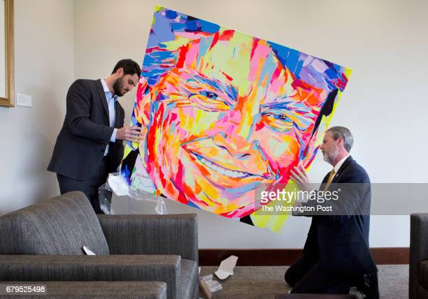 President of Liberty University Jerry Falwell Jr and his son Trey unwrap a portrait of Donald Trump gifted by a university donor in his office in...