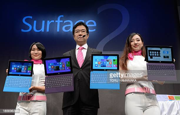 President of Microsoft Japan Yasuyuki Higuchi and models introduce the new tablet computer 'Surface 2' and 'Surface Pro 2' during a press conference...