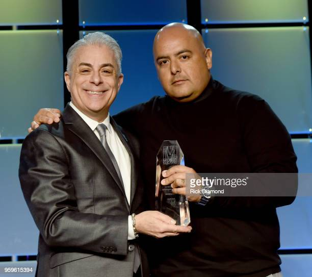 President of Music Business Association James Donio presents an award to Armando Rodriguez Senior VP of Universal Music Latin Entertainment onstage...