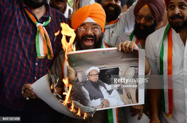 President of National Akali Dal party Paramjeet Singh Pamma burns a picture of Chief of the banned Pakistani Islamic charity JamatudDawa Hafiz...