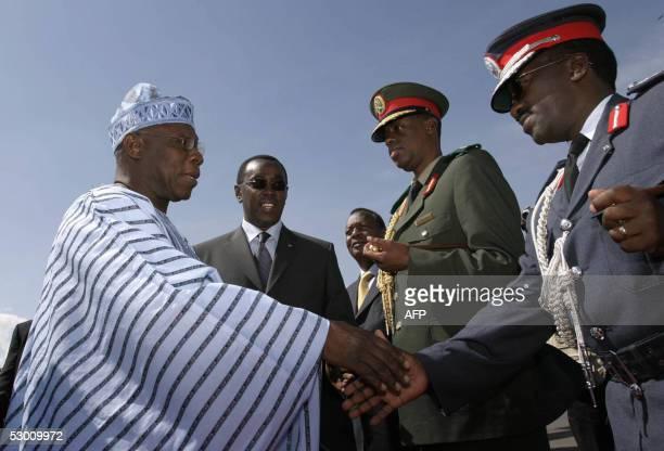 President of Nigeria Olusegun Obasanjo greets authorities 02 june 2005 accompanied by the Rwandan Prime Minister Bernard Makuza during a welcoming...