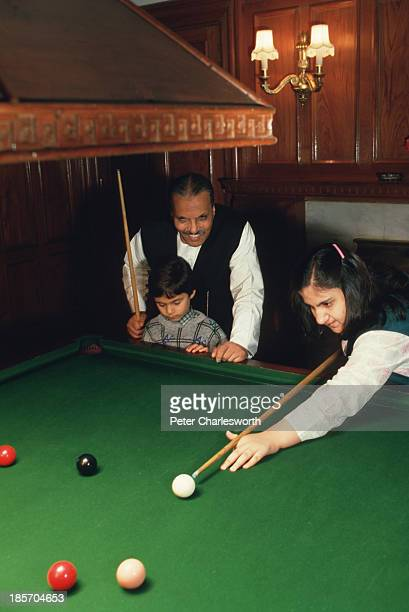 President of Pakistan General Mohammad Zia Al-Haq plays snooker with two of his grandchildren at his residence in Murree..