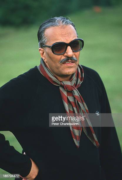 President of Pakistan General Mohammad Zia Al-Haq watches as another player hits a shot during a game of golf on a course near Murree.