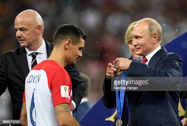 President of Russia Vladimir Putin presents Dejan Lovren of Croatia with his runners up medal following the 2018 FIFA World Cup Final between France...