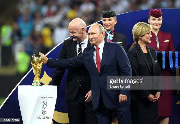 President of Russia Vladimir Putin touches the World Cup trophy as FIFA president Gianni Infantino looks on during the 2018 FIFA World Cup Final...