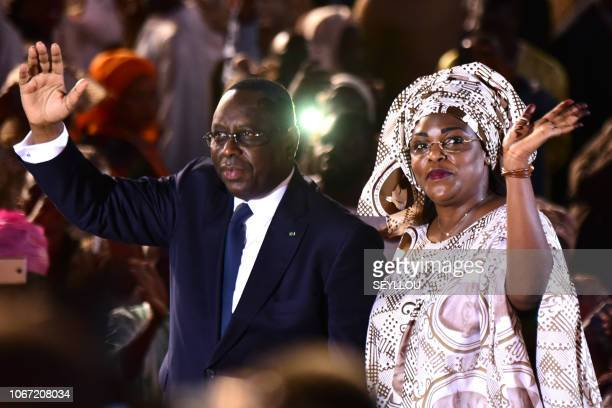 President of Senegal Macky Sall and his wife Marieme Faye Sall wave to people as they arrive at the Dakar Arena in Dakar on December 1 for the...