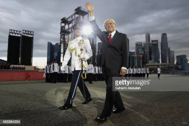 President of Singapore, Tony Tan Keng Yam waves to the audience after inspecting the guard of honour contingent during the National Day Parade at the...