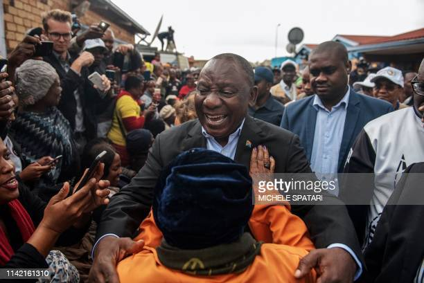 President of South Africa and the African National Congress Cyril Ramaphosa greets a voter as he arrives to cast his vote for the general elections...
