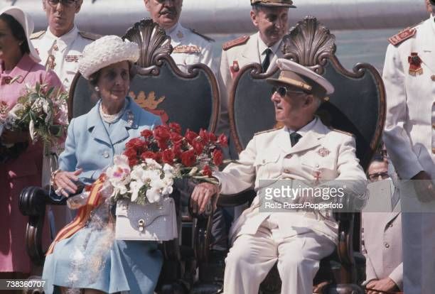 President of Spain General Francisco Franco pictured seated wearing full military dress uniform with his wife Carmen Polo at an official engagement...