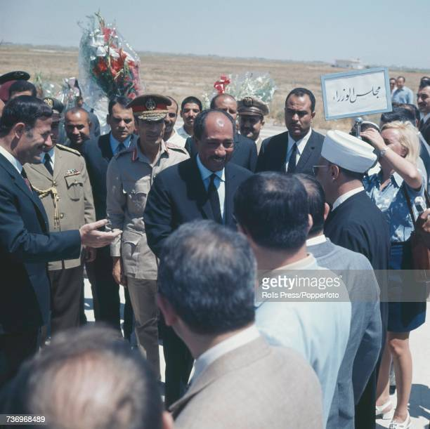 President of Syria Hafez alAssad on left holds out his hand to introduce Anwar Sadat President of Egypt and Muammar Gaddafi Premier of Libya to a...