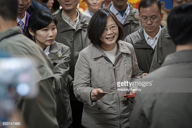 President of Taiwan Tsai Ing-wen hands out red envelopes containing NT$1 coin to visitors during a celebration blessing the new lunar Rooster year at...