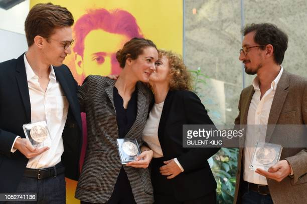 President of the Albert Londres Prize jury Annick Cojean kisses winner of the Albert Londres prize French journalist Elise Vincent next to others...
