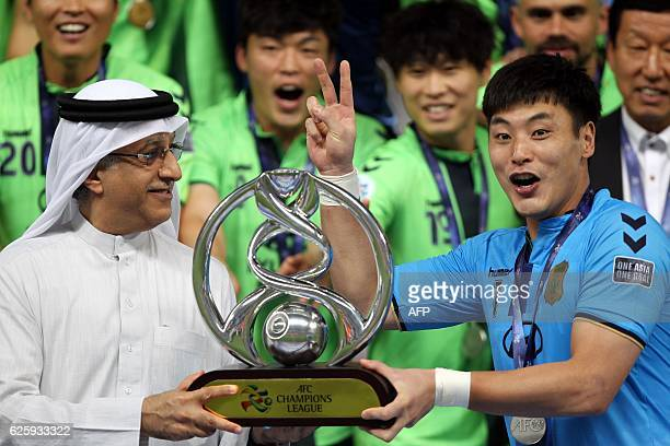 President of the Asian Football Confederation Shaikh Salman bin Ebrahim Al Khalifa presents Jeonbuk's captain Kwoun Suntae with the trophy following...