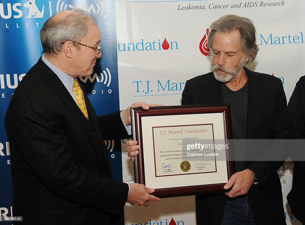 President of the Board of The T.J. Martell Foundation Ron Hartenbaum honors singer/musician Bob Weir with a plaque for his support at SIRIUS XM Studio on February 24, 2010 in New York City.