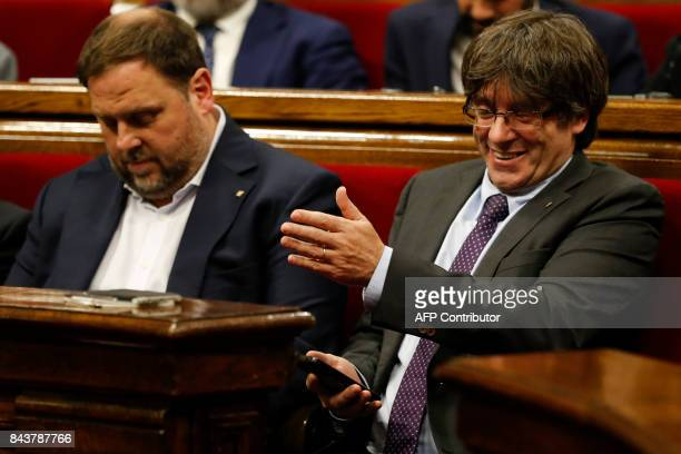President of the Catalan Government Carles Puigdemont gestures past Catalan regional vicepresident and chief of Economy and Finance and leader of the...