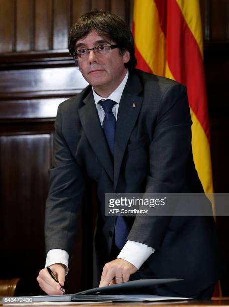President of the Catalan Government Carles Puigdemont signs a decree calling independence referendum at the Catalan Parliament in Barcelona on...