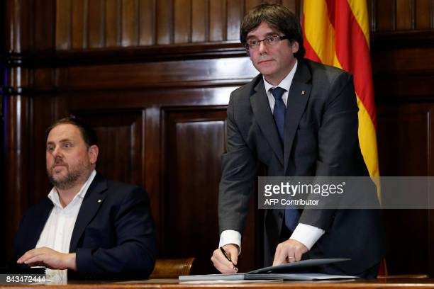 President of the Catalan Government Carles Puigdemont signs a decree calling independence referendum past Catalan regional vicepresident and chief of...
